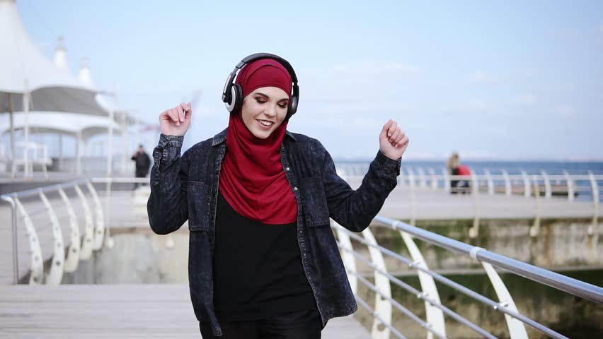 Modern muslim girl with hijab covering her head puts headphones on and starts walking somewhere enjoying and dancing to the music