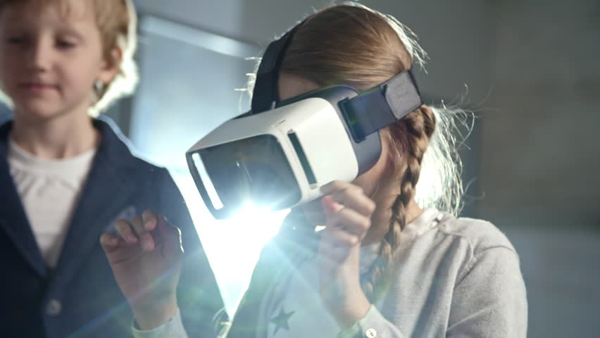 Primary school girl with two braids using virtual reality glasses as part of information technology lesson