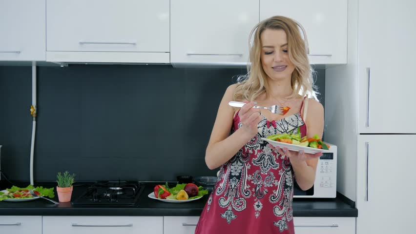 positive girl in nightdress and headphones eats and dances with a plate of salad in hands at kitchen