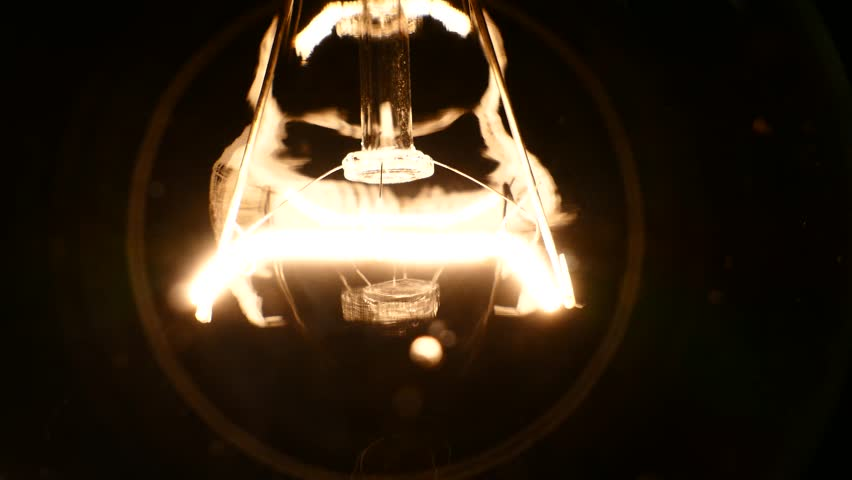 The incandescent lamp with a tungsten filament wobbles on the wire. The light flashes due to a poor contact. Electric power was lost in the room. Light from a light bulb. Bulb close-up.