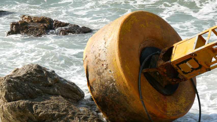 A large yellow buoy on the shores of azure sea. Waves hit the buoy