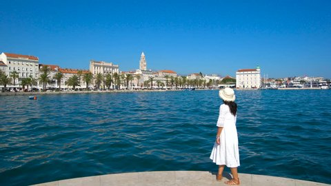 Woman traveller travels in Split,Croatia with panoramic view of Split old town. Split is the second-largest city of Croatia and prominent travel destination for historic center of Croatia cultures.