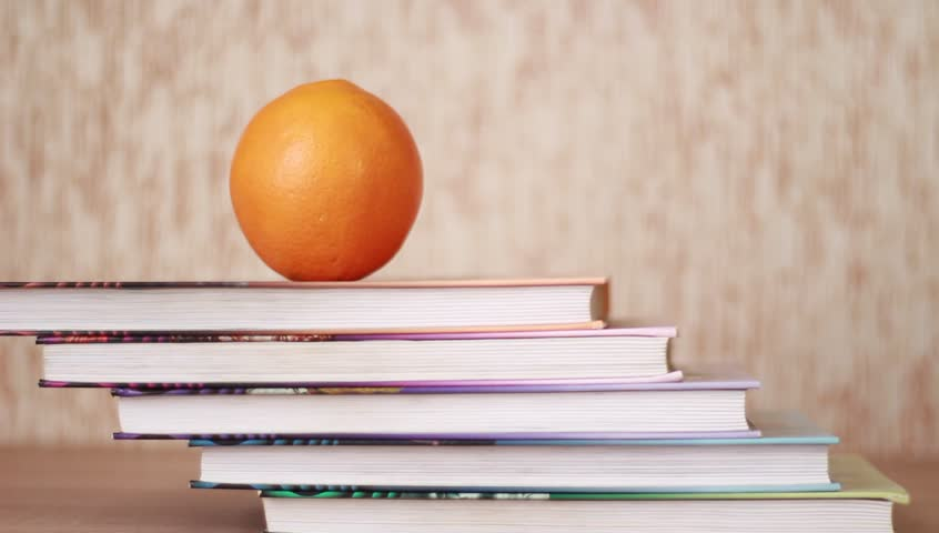 Hand going upstairs over books and taking orange