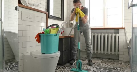 Woman is tired to cleaning tile in toilet. Woman holding a mop and cleaning floor in bathroom