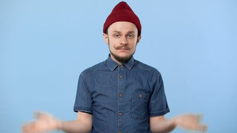 Portrait of hipster man 20s wearing hat and denim shirt throwing up hands and shrugging like have no clue, isolated over blue background. Concept of emotions