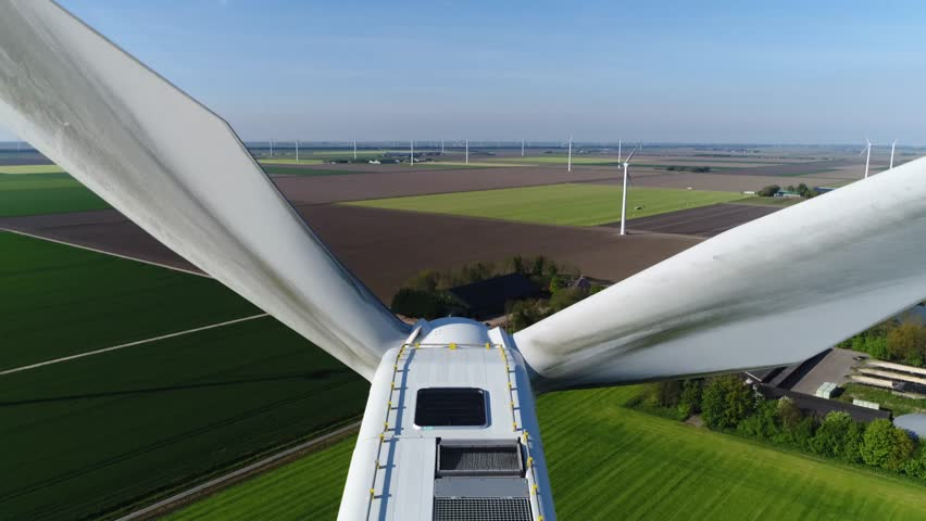 Aerial top down view wind turbine in polder landscape moving above the white modern construction of the wind turbine is device that converts winds kinetic energy into electrical energy 4k quality | Shutterstock HD Video #1008306526