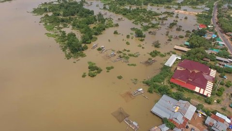 Aerial drone overhead of houseboats and chinese fishing nets on flooded river next to drowned village