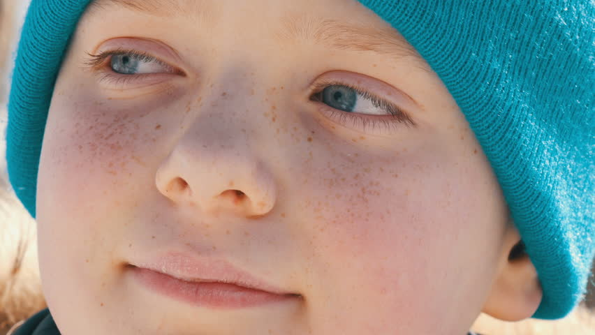 A boy with an unusual color of turquoise eyes and freckles on his face in a blue hat looks aside | Shutterstock HD Video #1008347776