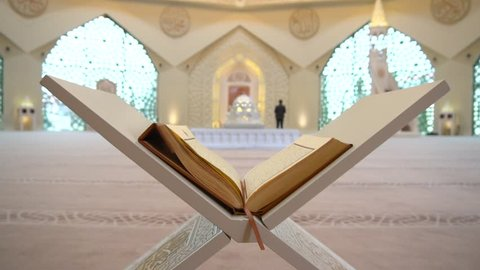 A Muslim man reads a koran or quran in an Islamic mosque