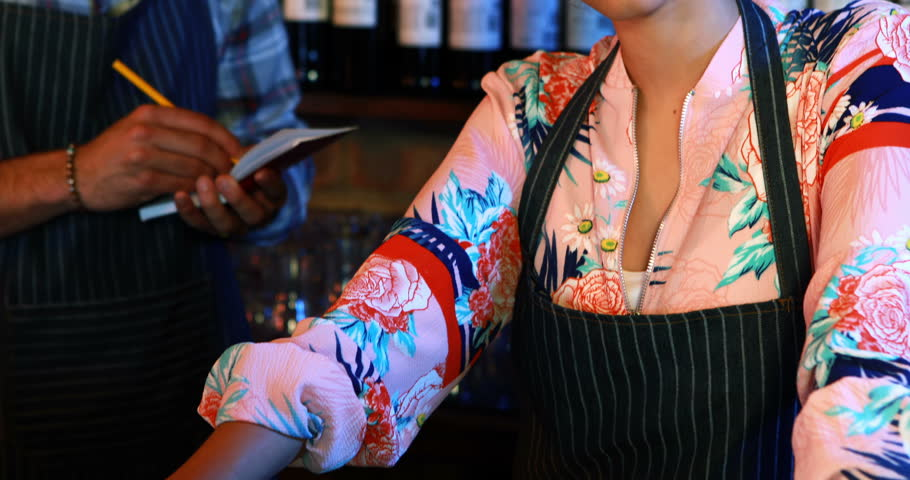 Portrait of smiling barmaid with barman in background in pub