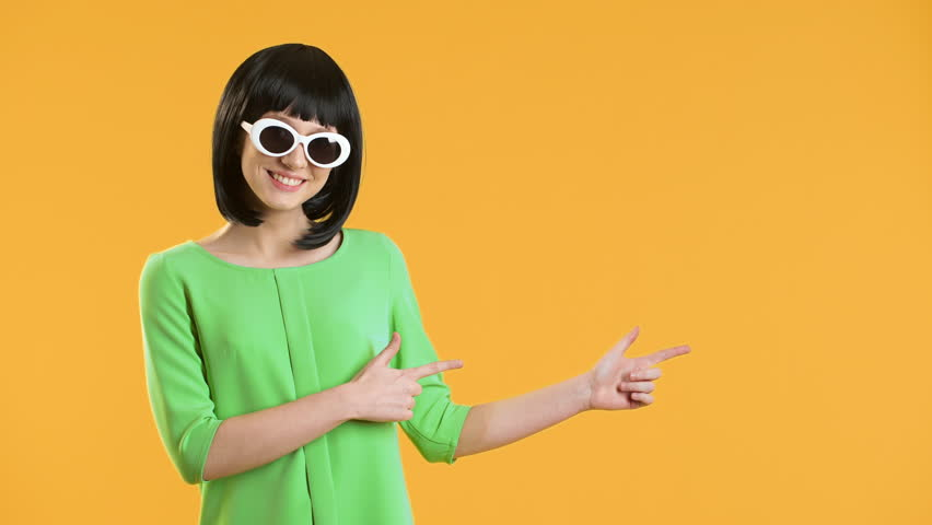 Portrait of caucasian woman with bob hairstyle wearing disco sunglasses smiling and pointing finger on copy space, over yellow background. Concept of emotions