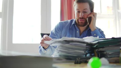 A Man In Debt Makes Phone Call, Concerned And Stressed With Bill Letters