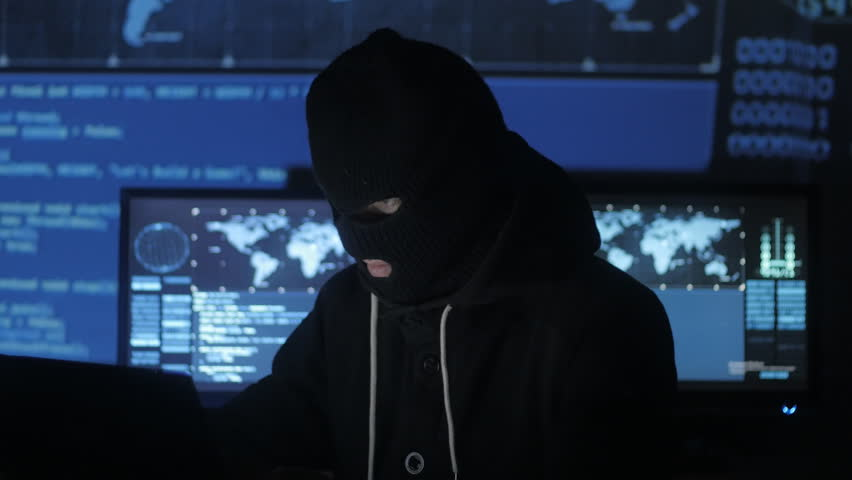 Dangerous hacker in the mask tries to enter the system using codes and numbers to find out the security password. The concept of cybercrime. | Shutterstock HD Video #1008364966