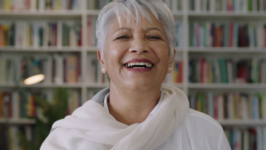 Portrait of friendly indian middle aged teacher laughing standing in library books education | Shutterstock HD Video #1008365626