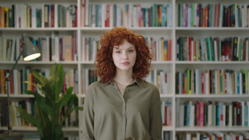portrait of cute young librarian woman standing in library attractive student smiling close up red head
