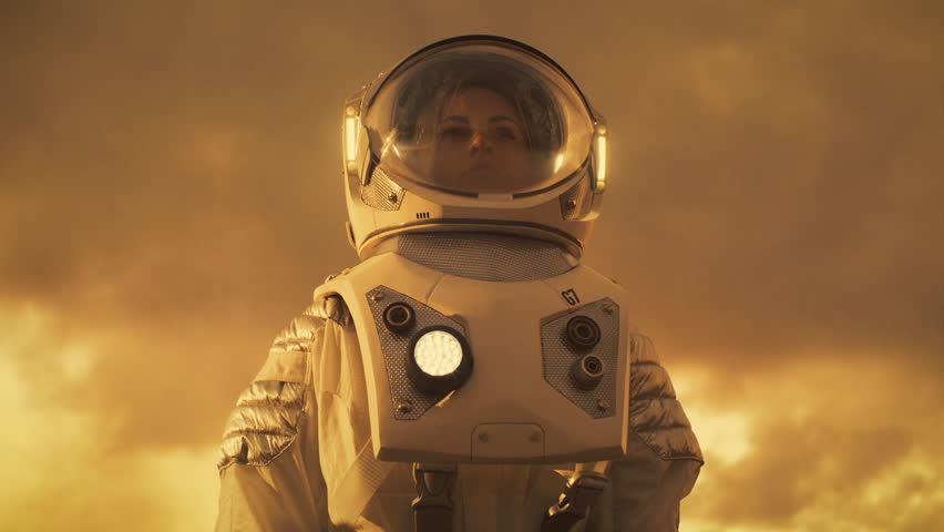 Low Angle Shot of Female Astronaut in the Space Suit Looking Around Alien Planet. Red and Orange Planet Similar to Mars. Advanced Technologies, Space Travel, Colonization Concept.  RED EPIC-W 8K.