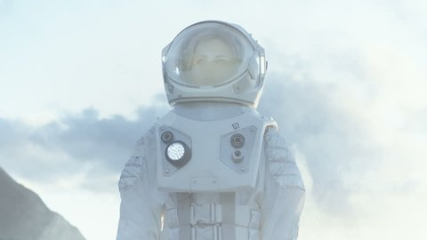 Medium Shot of Female Astronaut in the Space Suit Looking Around Frozen Alien Planet. Advanced Technologies, Space Travel, Colonization Concept. Shot on RED EPIC-W 8K Helium Cinema Camera.