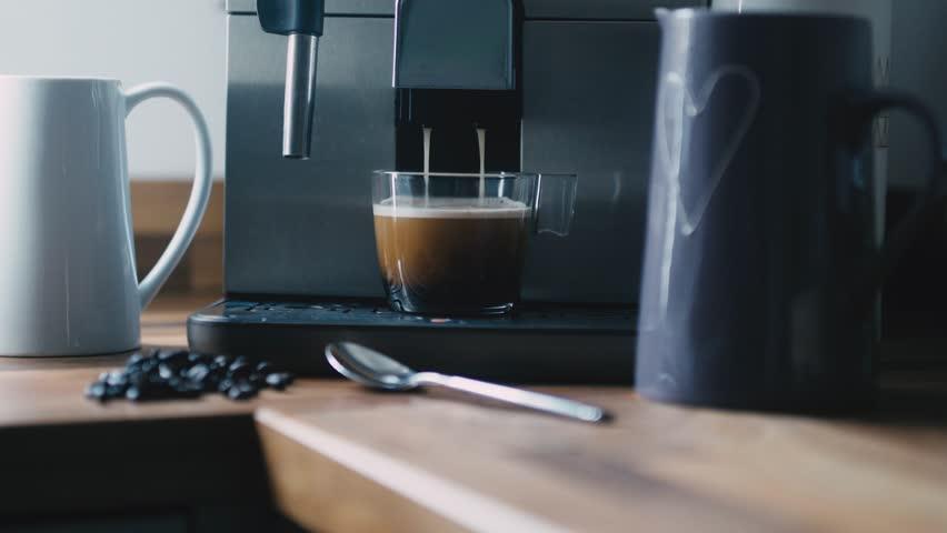 Coffee machine pouring espresso into cup
