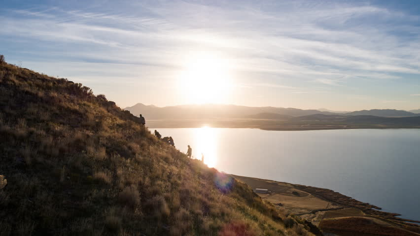 Aerial view flying past hikers climbing rocky path to view wide open landscape and lake at sunset. | Shutterstock HD Video #1008388156
