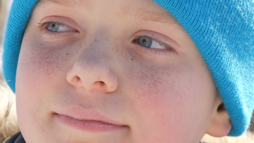 Boy teenager with sky blue eyes and freckles on his face in a blue hat looks into the distance | Shutterstock HD Video #1008397306