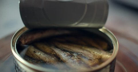 Using fork takes a smoked sardines from a tin can