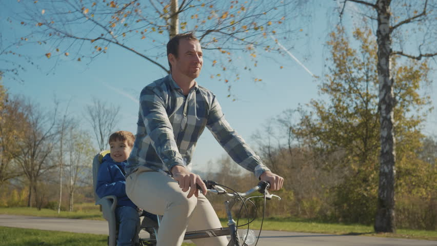 Tracking shot - Father and son spending time together talking on a bicycle ride having fun on a sunny day in the park.