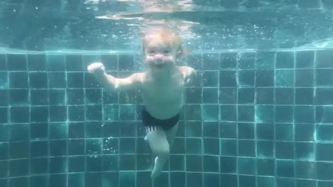 Happy smiling toddler is jumping and diving under the water in the swimming pool. An underwater shot.