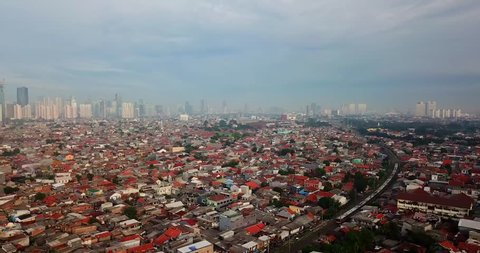 Stunning aerial landscape of crowded slum residential houses beside railroad tracks in Jakarta city, Indonesia. Shot in 4k resolution