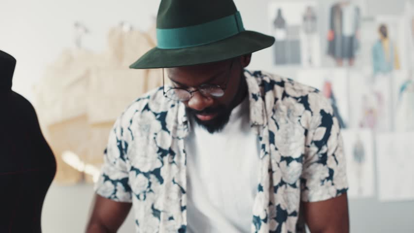 Handsome bearded Afro-American dressmaker in a flowered shirt casually throws the measuring tape around his neck, looks straight to camera. Cozy, modern office. Fashion sketches on the background