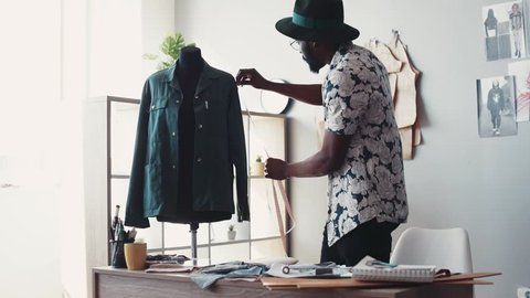 Tailor at work, measures the long sleeve with measuring line, writes down the numbers into his notepad. Modern, creative fashion studio. Trendy clothes, new collection, being busy. Slow motion