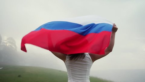 Russian girl running with flag in a beautiful landscape