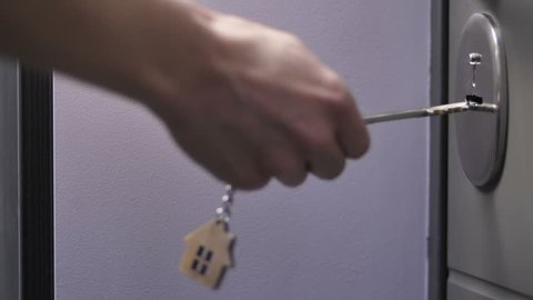 Close-up slow motion shot of female hand holding door keys with wooden house shaped key ring. Woman locking or unlocking door of her house or apartment.