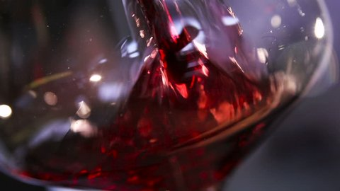Sauvignon, cabernet or merlot splashing slow motion closeup. No people, food and drink concept of advertising, delicious footage of grape liquor juicy vinous color poured in classic wineglass