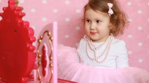 Beautiful little girl dresses up, puts on beads and looking in the mirror. A cute child fashionista plays a real lady. Pink glamor background and children's chest of drawers