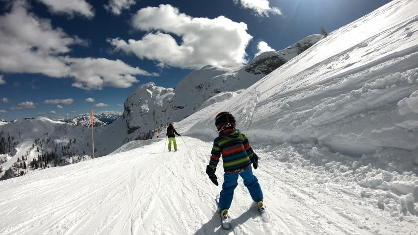 Little boy skiing in the Alpine resort. A 5 year old child enjoys a winter holiday with his mother. Stabilized footage. Slow motion.  | Shutterstock HD Video #1008519346