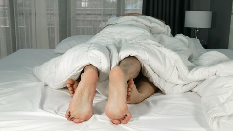 4k of couple feet seen from under blanket on a bed