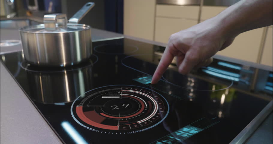 Close up of a man who cooks in his own home on a stove of the latest technology and regulates power and intensity thanks to holography. Concept of: future, technology, kitchen, augmented reality.