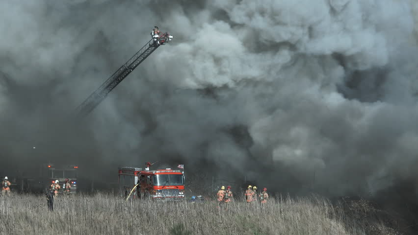 Fire fighters have their work cut out for them as they try to contain a huge fire during high winds causing black smoke.