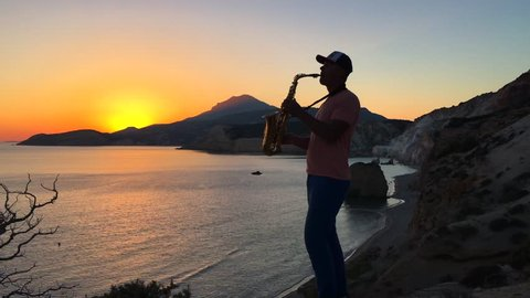 The saxophonist plays in the rays of the sunset on a cliff overlooking the sea