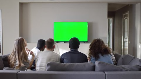 Rear view of young men and women sitting on couch and watching sport match on chroma key TV screen. Friends standing up, raising hands and embracing while celebrating goal