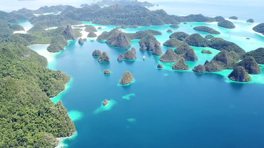 Eroded limestone islands rise from an amazing, tropical lagoon in Wayag, Raja Ampat, Indonesia. This unique, equatorial region is best known for its vast array of marine biodiversity.