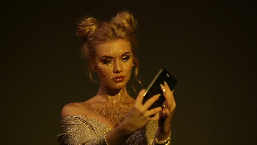 Beautiful woman blowing gold glitter