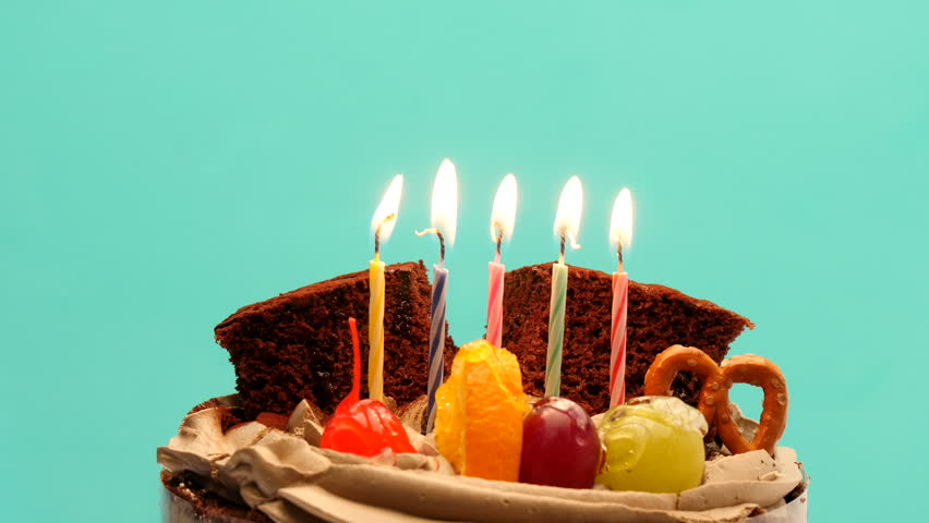 Rotate Celebration Cake With Burning Candles On A Light Green Background