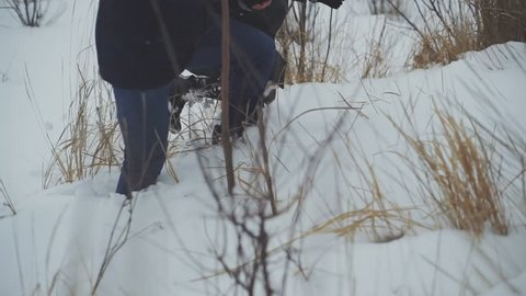 coule of ornithologists walk through deep snow and snowdrifts to a bird's nest on a tree