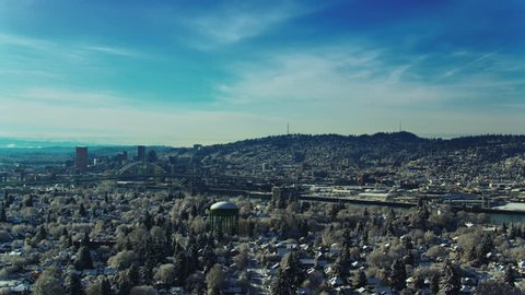 Aerial view panning left of early morning sun with Portland waterfront and downtown Portland in the distance on a blue sky winter morning after a snow