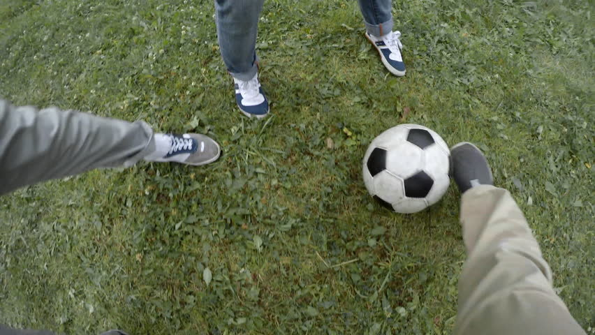 Point of view shot of primary school boy dribbling ball when playing football with friends, some of them falling down | Shutterstock HD Video #1008648826