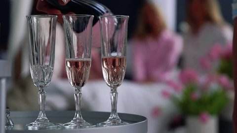 Close-up of a beautiful girl fills with champagne glasses for girlfriends who have fun in the background at a bachelorette party. Pajama party with alcohol.