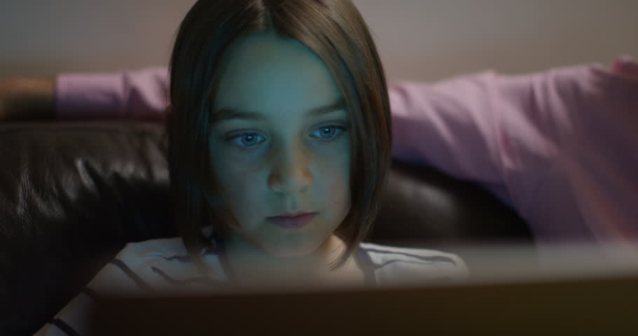 4K Close up on face of little girl, watching computer screen & reacting with surprise. Slow motion.   Shutterstock HD Video #1008651826