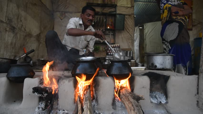 NAGPUR, MAHARASHTRA, INDIA 16 JANUARY 2017 : Unidentified people making and cooking / baking fresh food in a rural village in vintage kitchen using firewood in earthen chulhas.