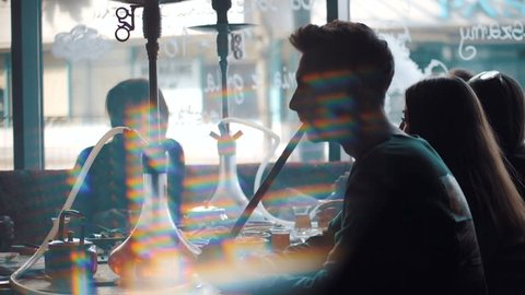 Young company is having fun and eating in bar. smoking a hookah, communicating in an oriental restaurant. Lebanon cuisine served in restaurant.